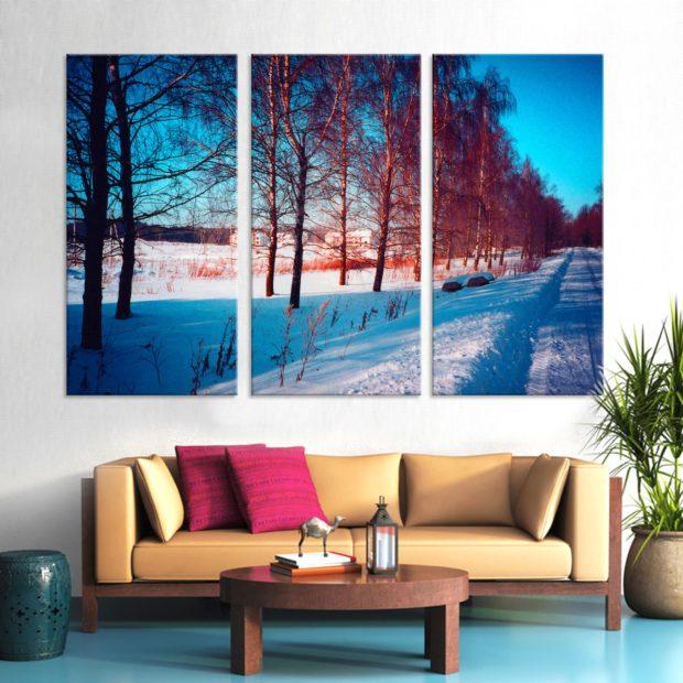 Гостиная со светлым диваном, круглым столиком и модульными картинами на стене